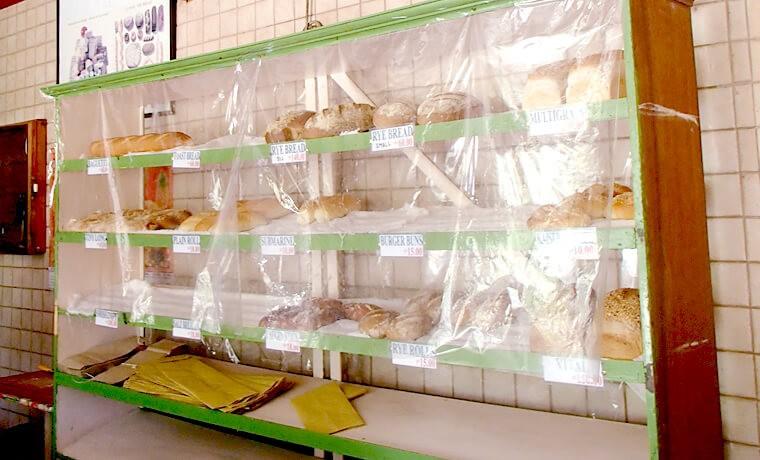 奥の棚にはプレーンな味のパンが並びます。食パンやフランスパンにサンドイッチ・ハンバーガー用のバンズなど。価格は小さいもので10ペソから、一斤で150ペソの値札がついていました