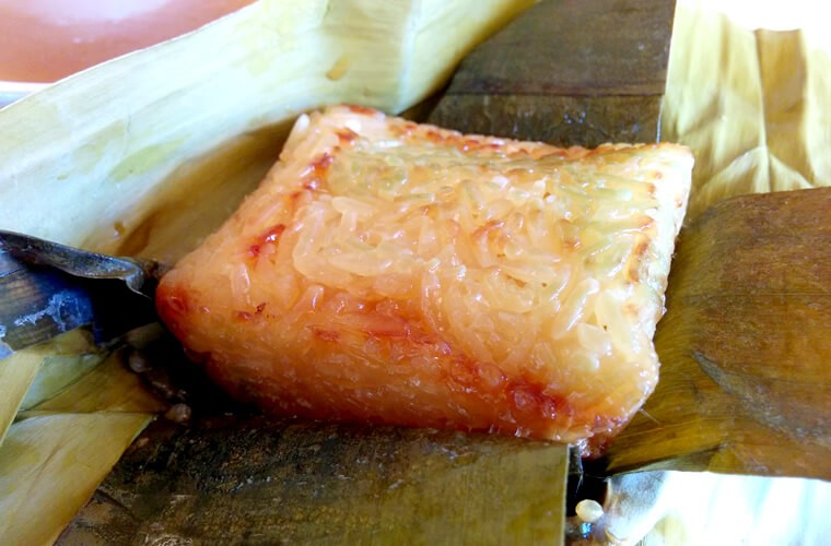ココナッツミルクの甘さともち米の香りがなんとも言えない、素朴な味わいが美味しいスーマン。うすく緑の部分はバナナの葉の色が移っただけなので、安心して食べられます。