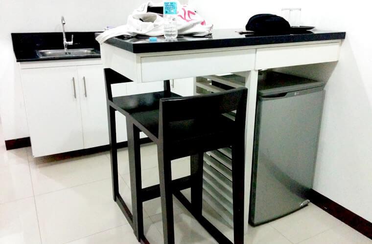 テーブルに冷蔵庫・小さいキッチン付きのお部屋です。